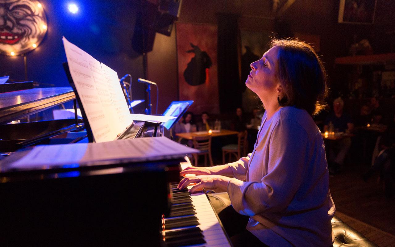 Marina Albero sitting playing the piano at the Royal Room