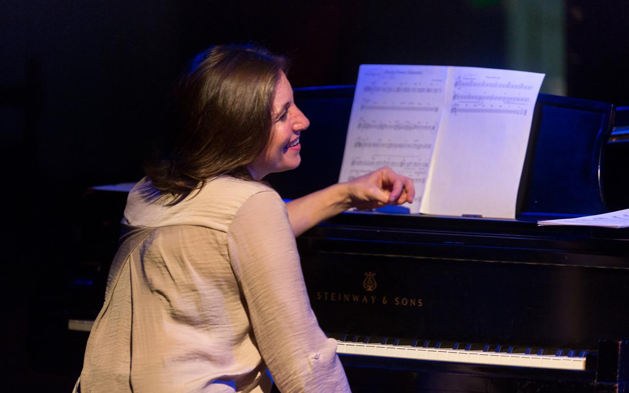 Marina Albero sitting at a piano smiling