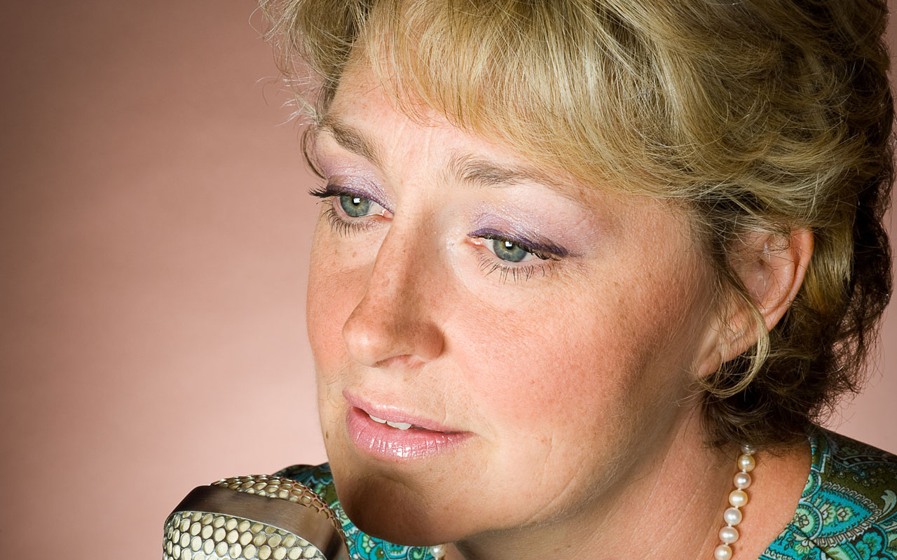 Jazz vocalist Greta Matassa singing into a microphone