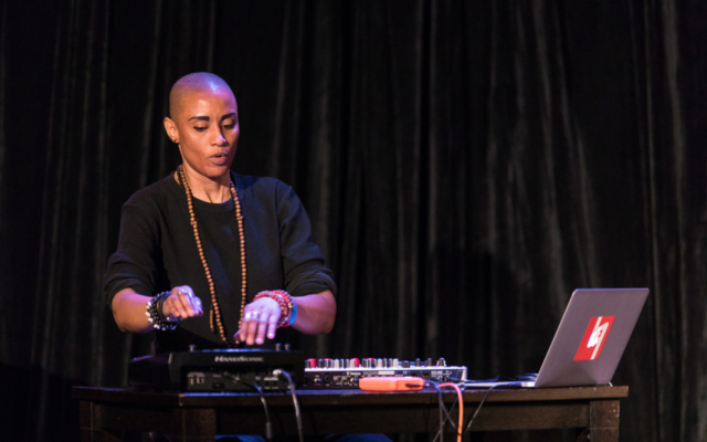 Val Jeanty playing electronic percussion instruments.