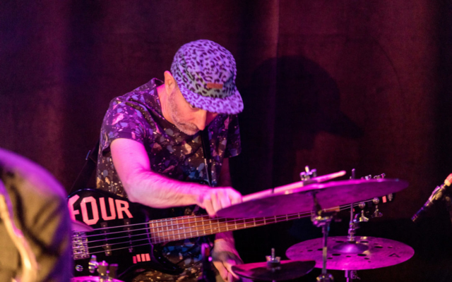 Nate Wood skillfully plating the drums while holding his guitar.