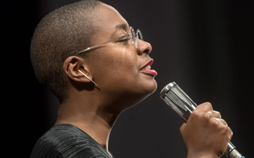 Cécile McLorin Salvant singing, holding a microphone