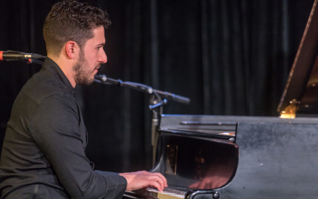 Emmet Cohen playing the piano.