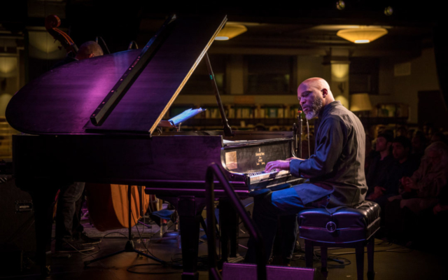 Orrin Evans playing the piano bathes in purple light.
