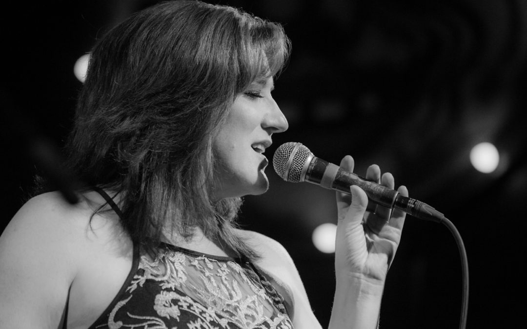 Nancy Erickson singing and holding microphone