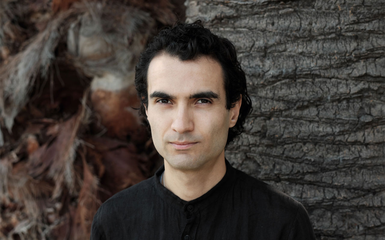 Tigran Hamasyan standing in front of a tree