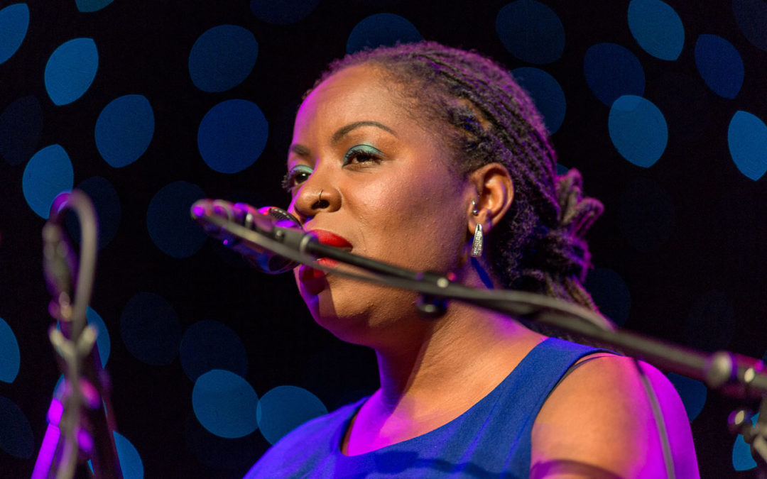 Johnaye Kendrick singing into a microphone