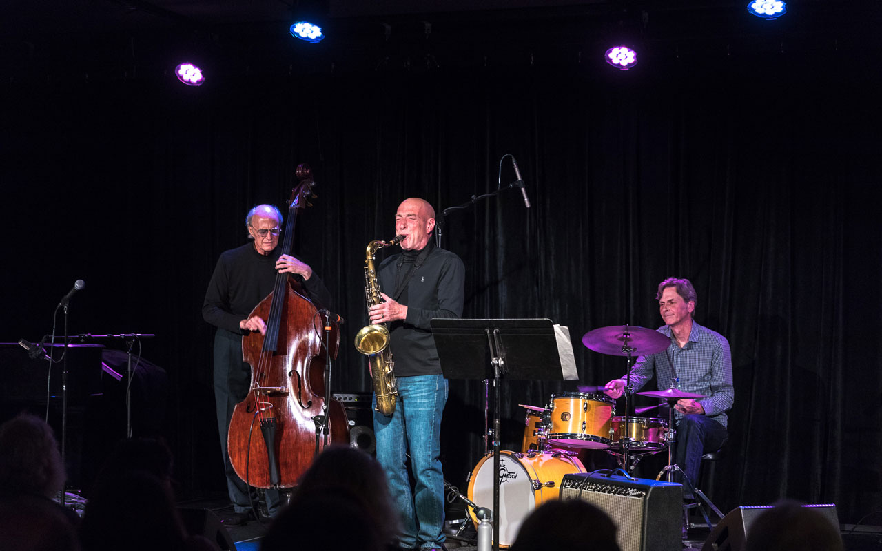 Three jazz musicians playing bass, saxophone, and drums.