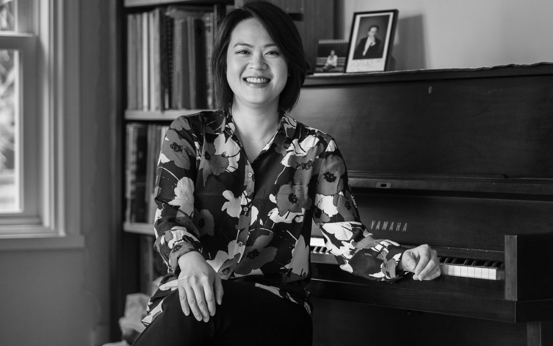 Julia Tai smiling and sitting in front of a piano.