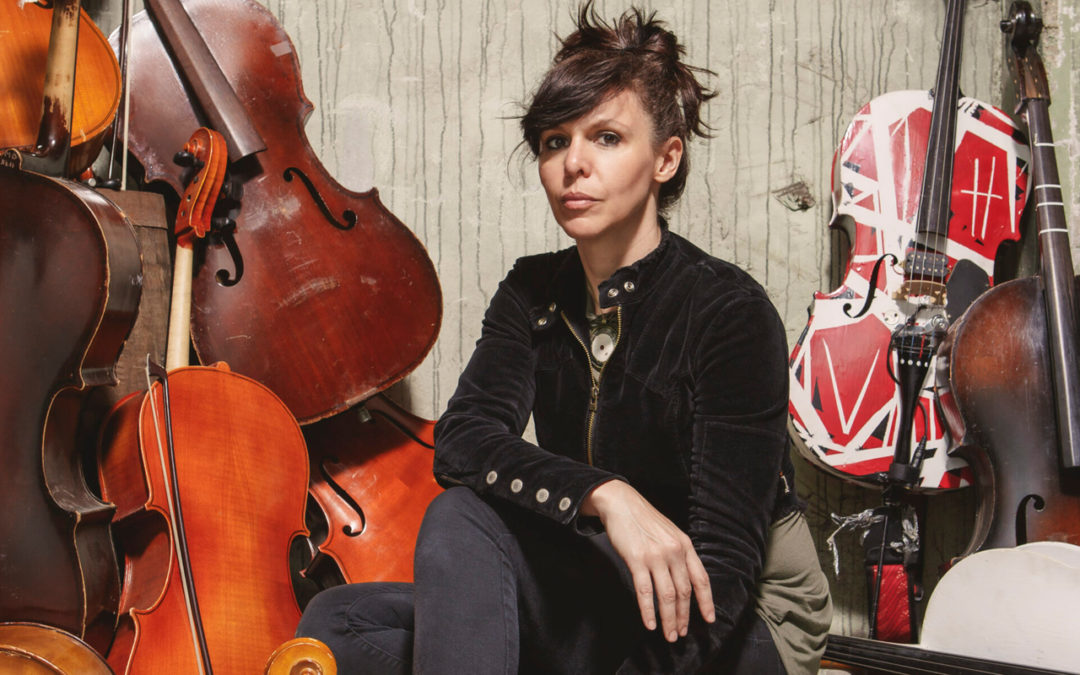 Helen Gillet surrounded by cellos.