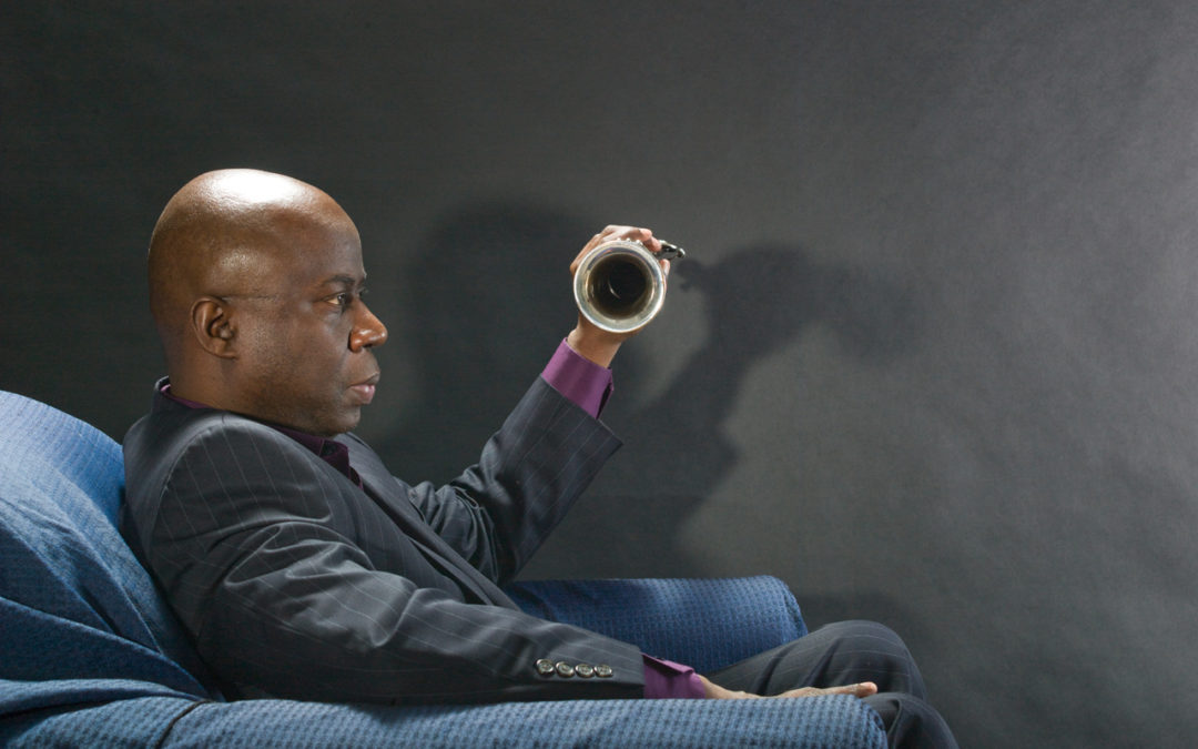 Sam Newsome sitting in profile with his saxophone.