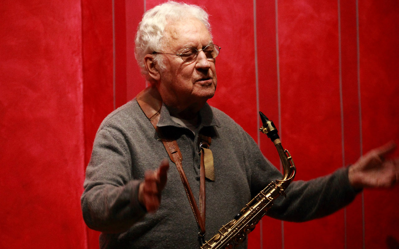 Lee Konitz with saxophone around his neck and arms extended in an open gesture