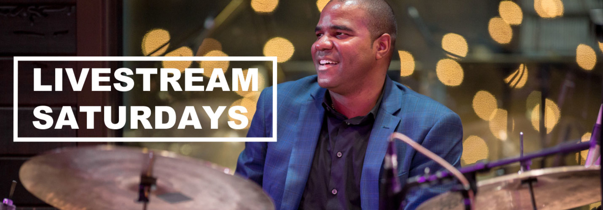 D'Vonne Lewis playing drums and smiling