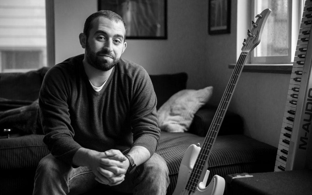 Tarik Abouzied sitting with a bass guitar