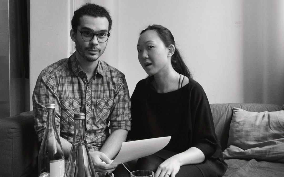 Fabian Almazan and Linda May Han Oh sitting on a couch with a piece of paper in hand