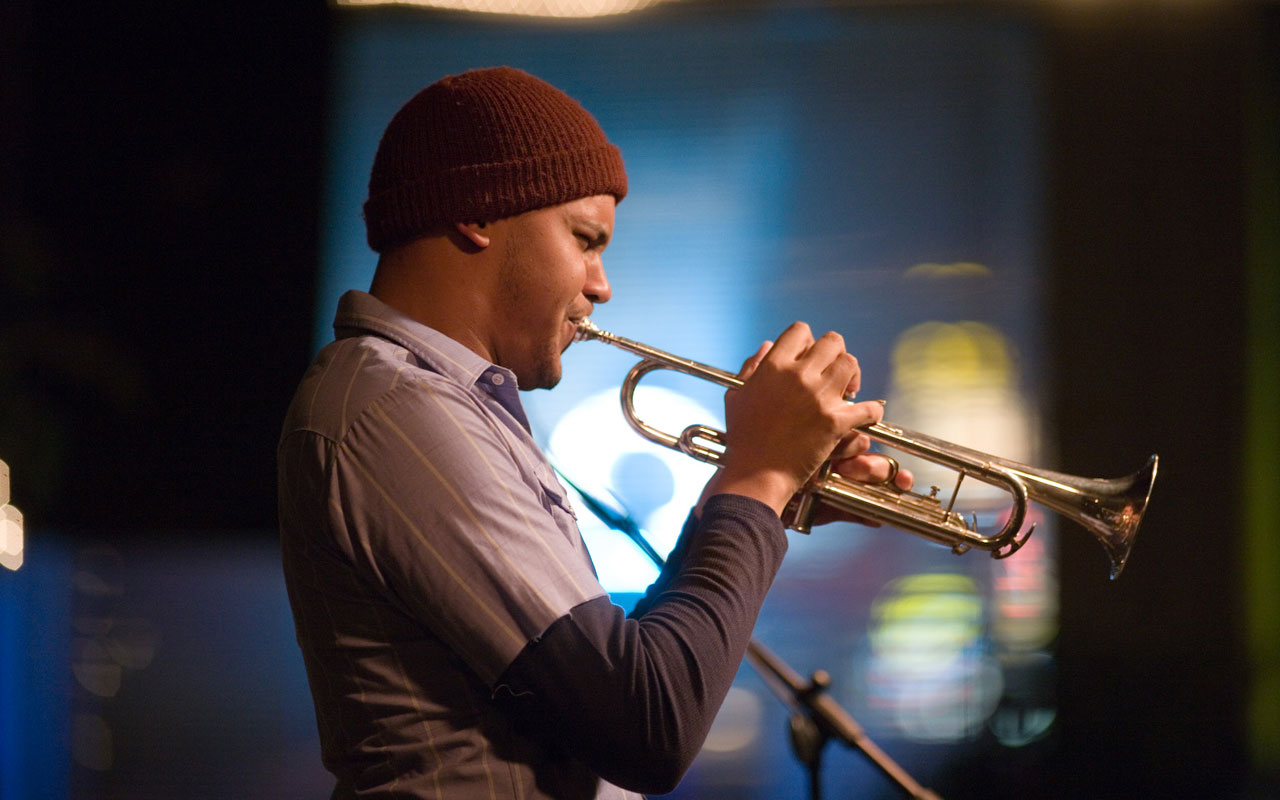 Ahamefule Oluo in profile wearing a brown beanie playing the trumpet.