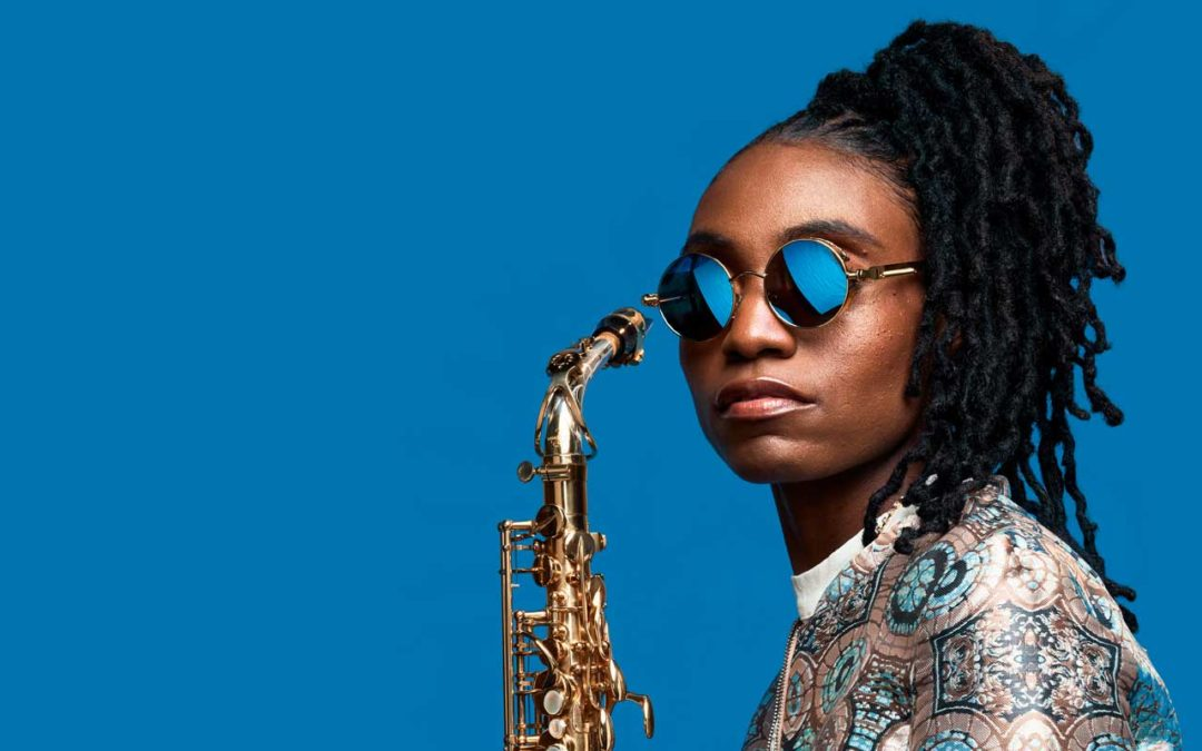 Lakecia Benjamin holding a saxophone while wearing blue reflective sunglasses.