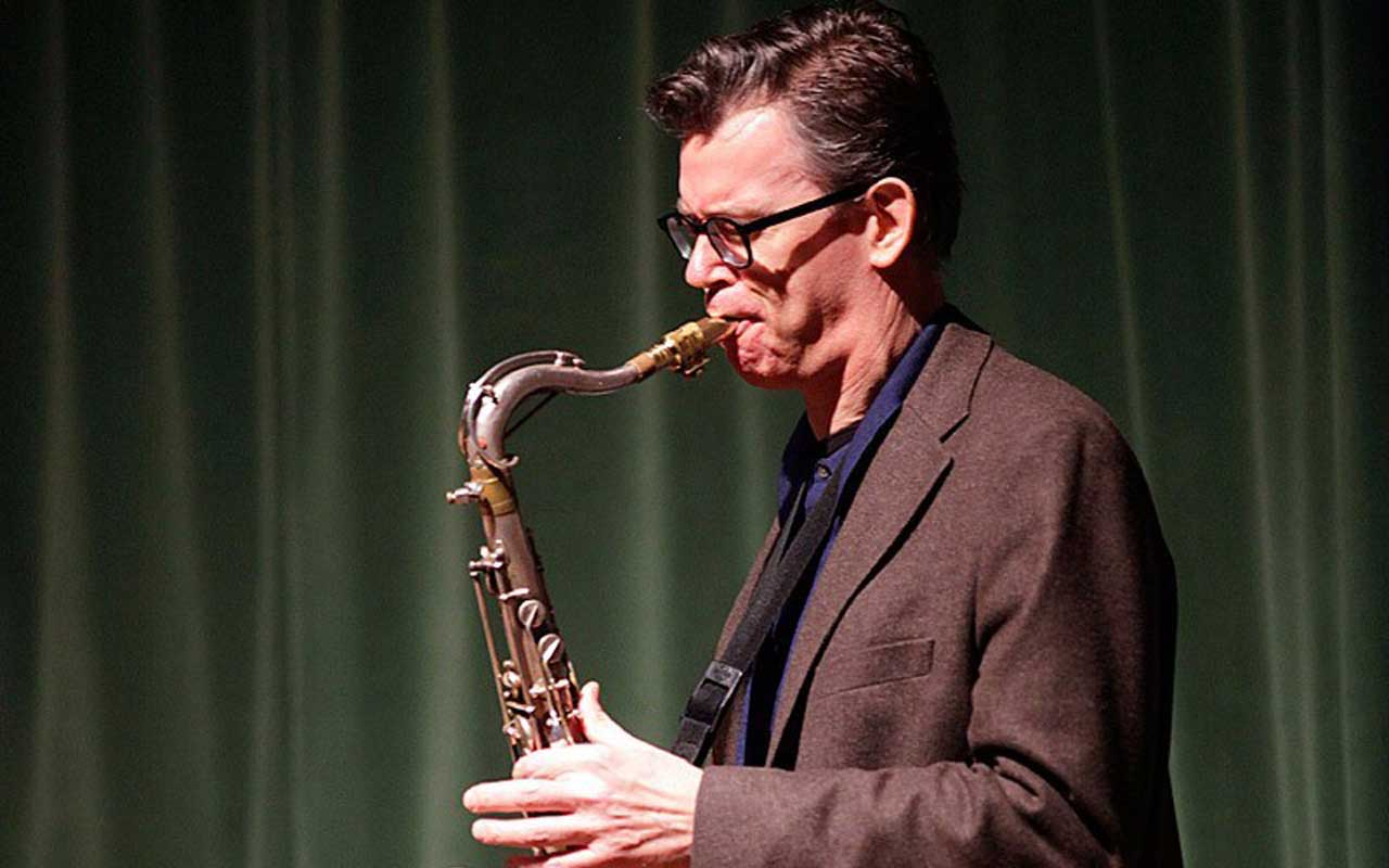 Ab Baars playing a saxophone in front of a green curtain