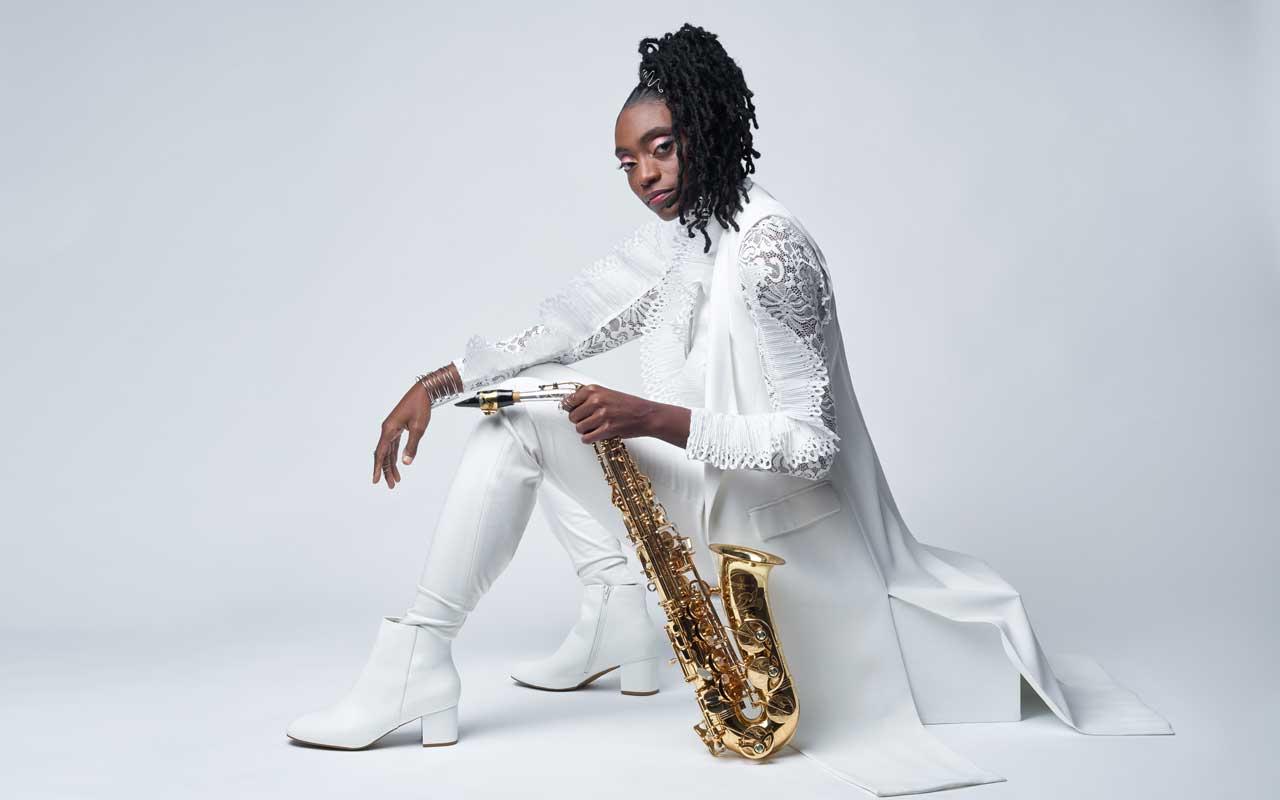Lakecia Benjamin sitting holding a saxophone.
