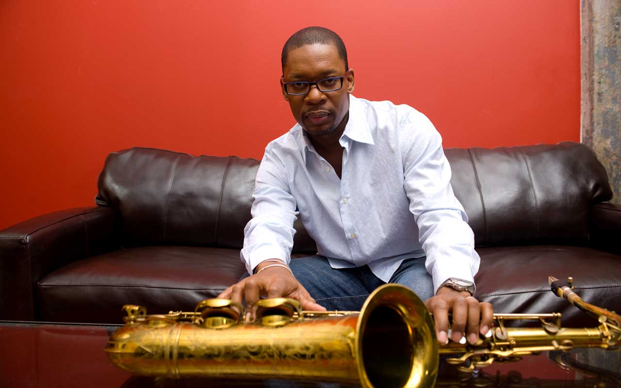 Ravi Coltrane sitting on a couch with a saxophone resting on a table in front of him.