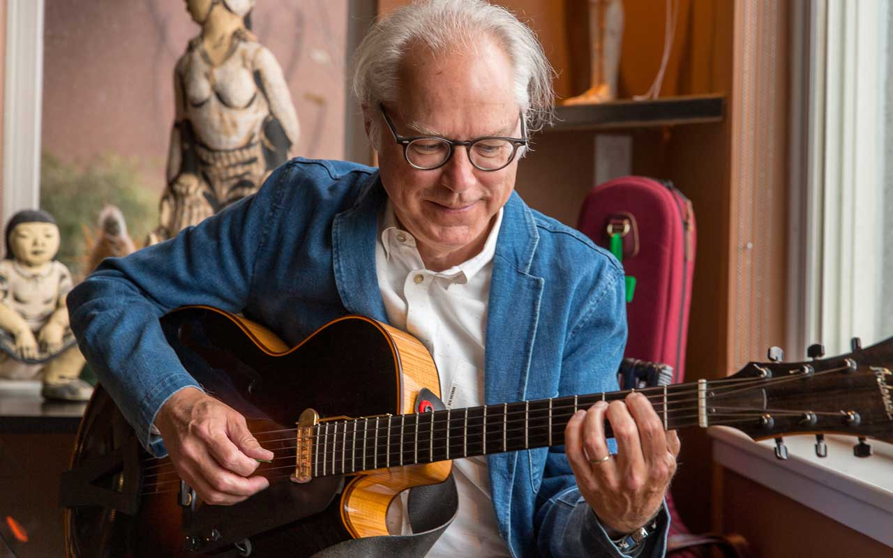 Bill Frisell sitting in a living room playing a guitar