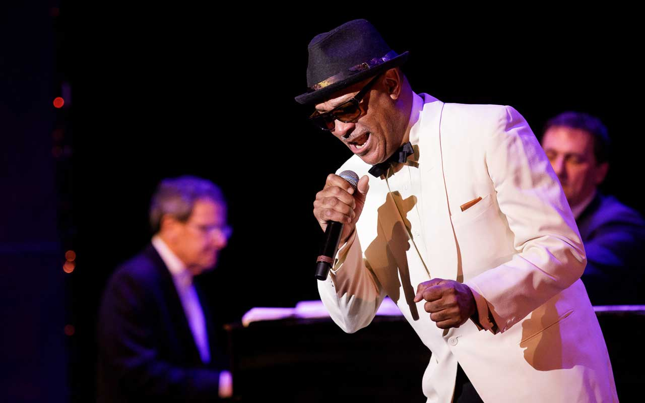 Reggie Goings singing on stage in a white tuxedo
