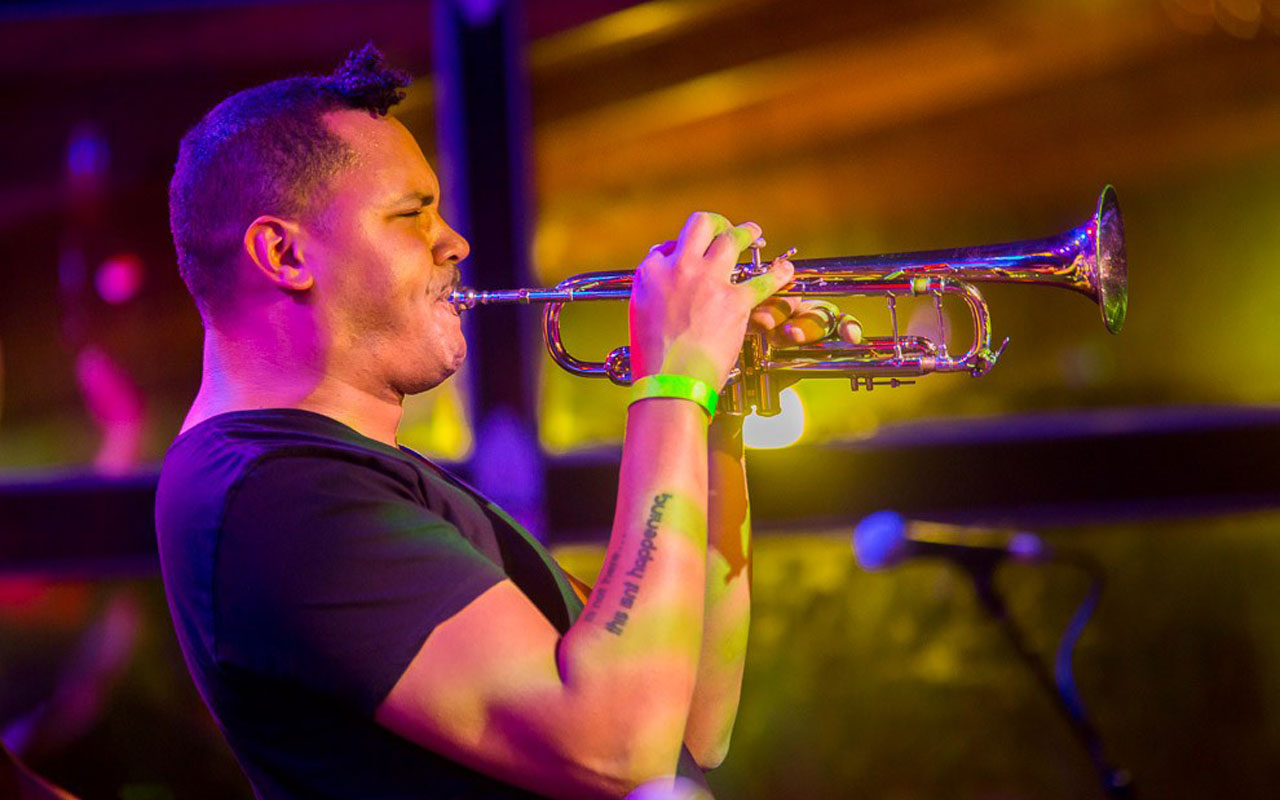 Ahamefule J. Oluo playing a trumpet on stage