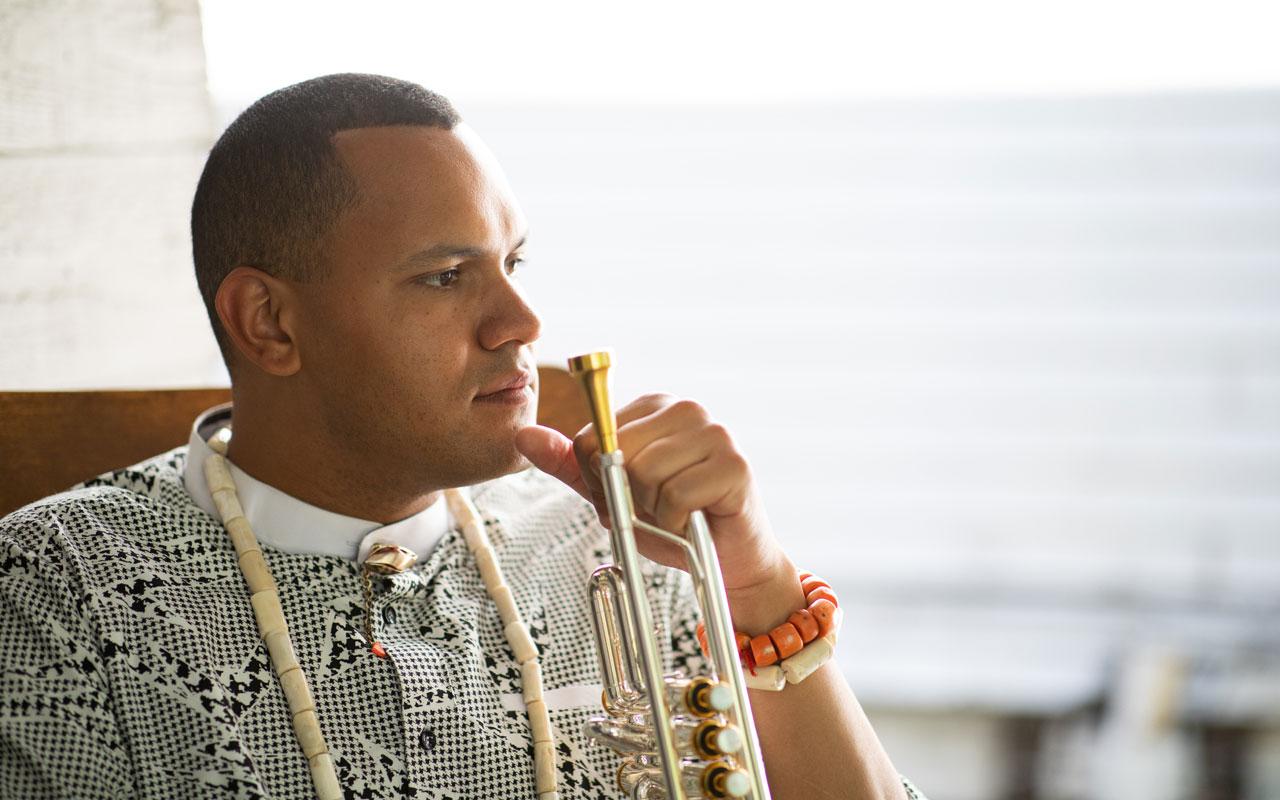 Ahamefule J. Oluo sitting holding a trumpet