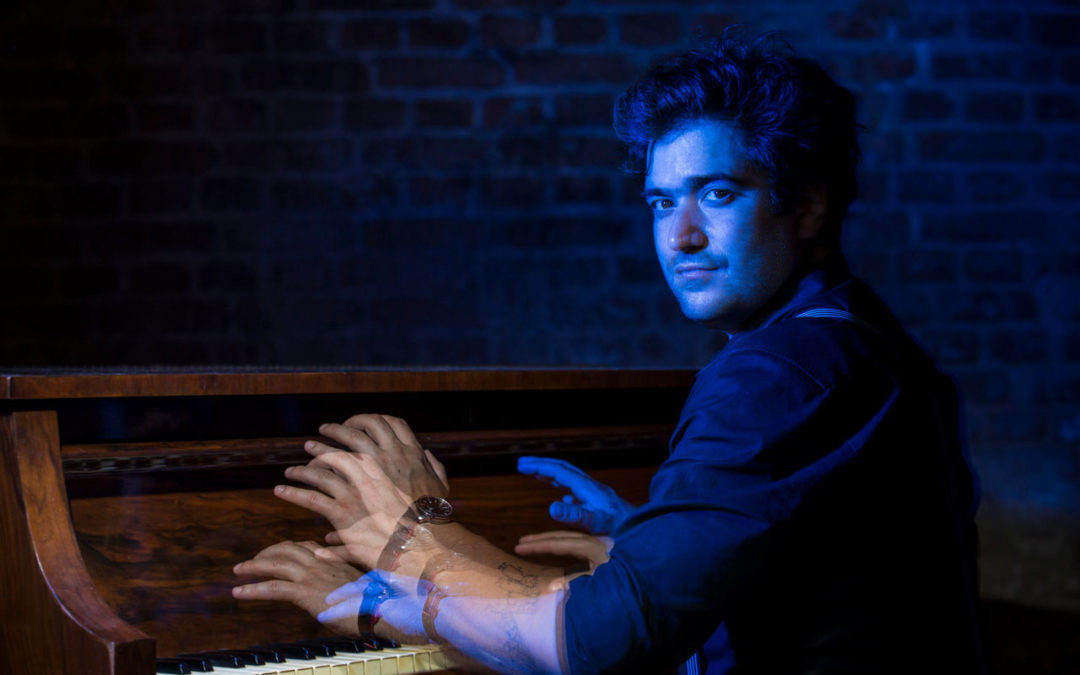 Harold Lopez Nussa playing the piano bathed in blue light