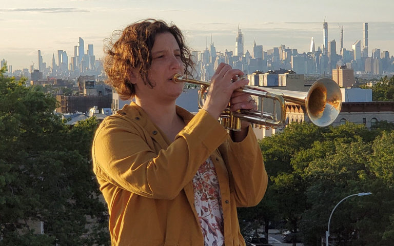 Samantha Boashnack playing a trumpet with the Seattle cityscape in the background.