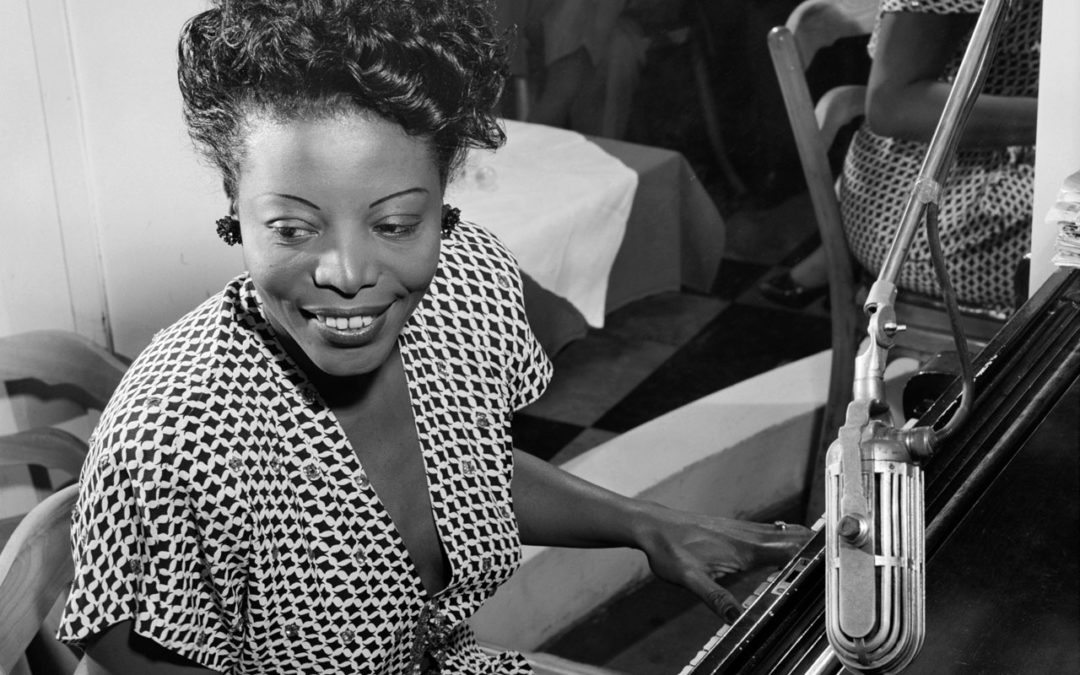 Mary Lou Williams seated at the piano, playing and smiling.
