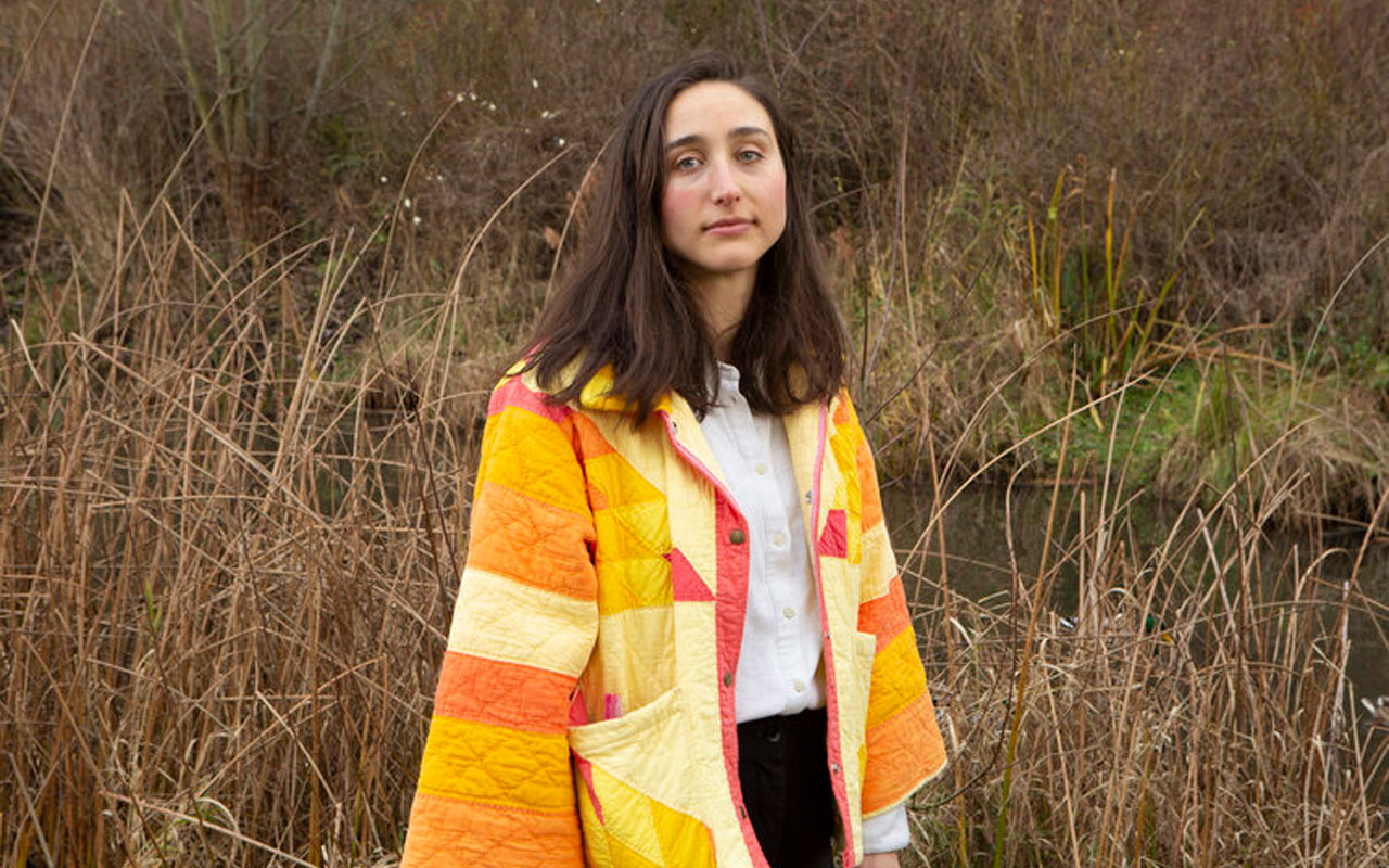 Abbey Blackwell wearing a colorful patchwork jacket, standing in front of wild grass.