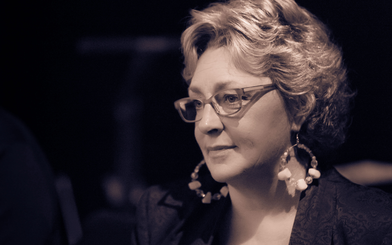 Greta Matassa wearing glasses and large round earrings, looking to the side at an angled profile.