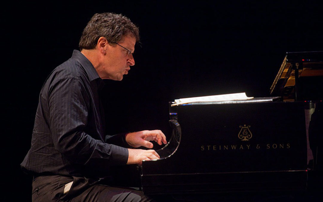 Randy Halberstadt playing piano in profile.