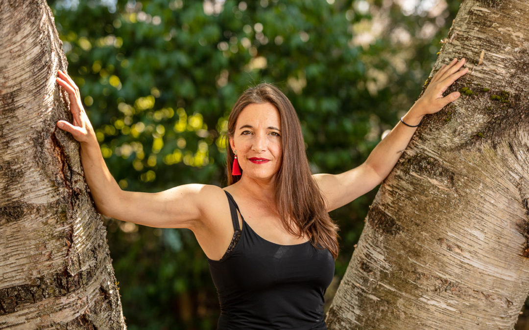 Marina Albero dressed in a black spaghetti strap top and bright red earrings, standing between two trees.