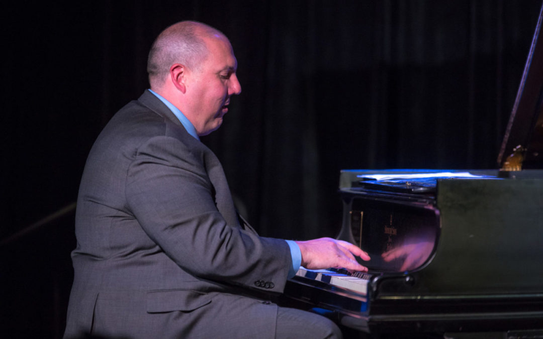 Eric Velinde wearing a suit, playing the piano in profile.
