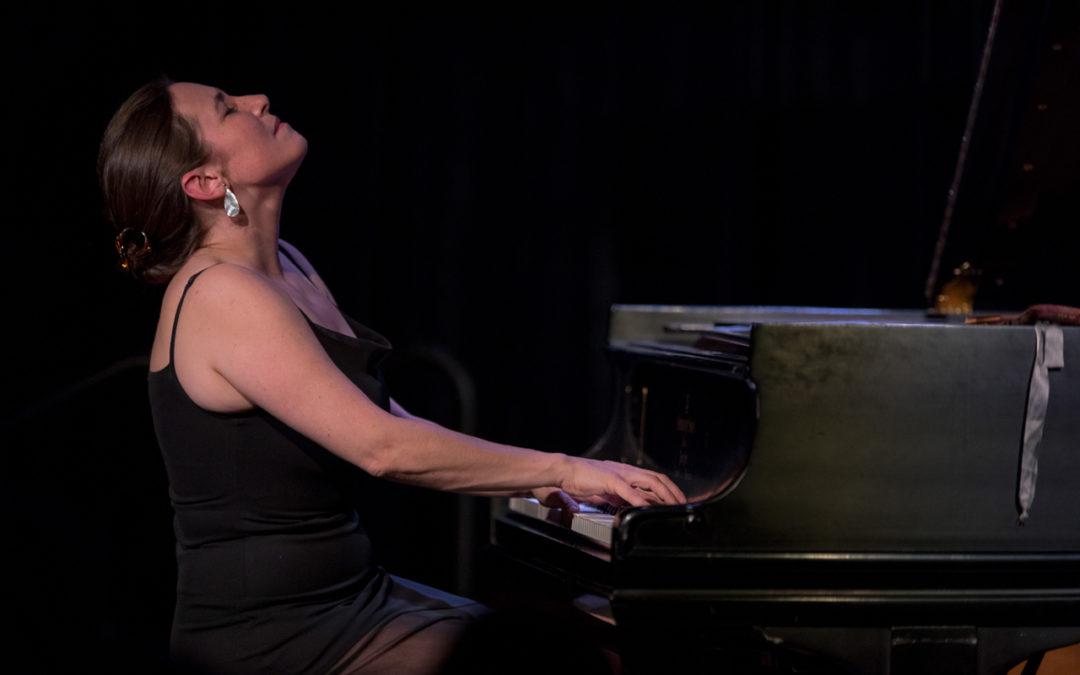 Marina Albero dressed in black, playing the piano.